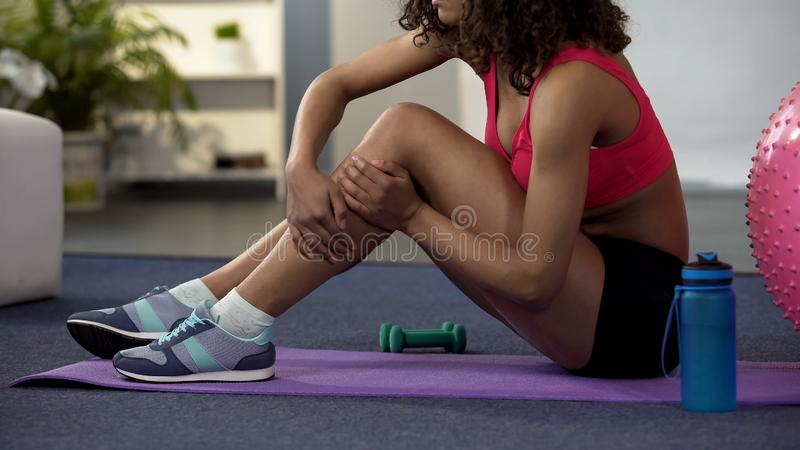 Girl in gym outfit sitting on floor and massaging cramped leg, strained muscle. Stock photo stock image