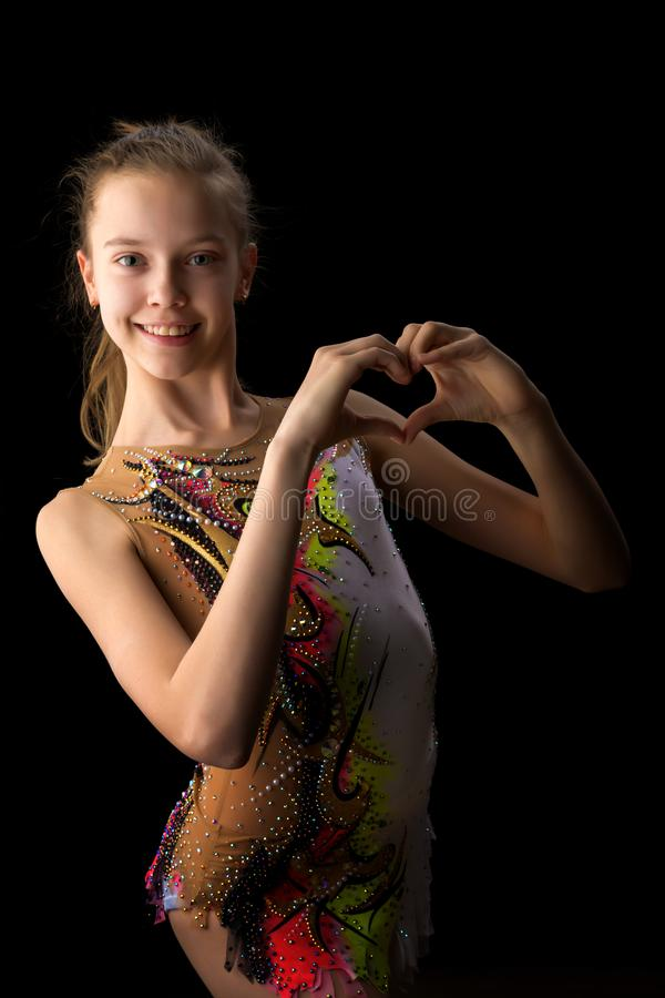 Girl gymnast on a black background royalty free stock image