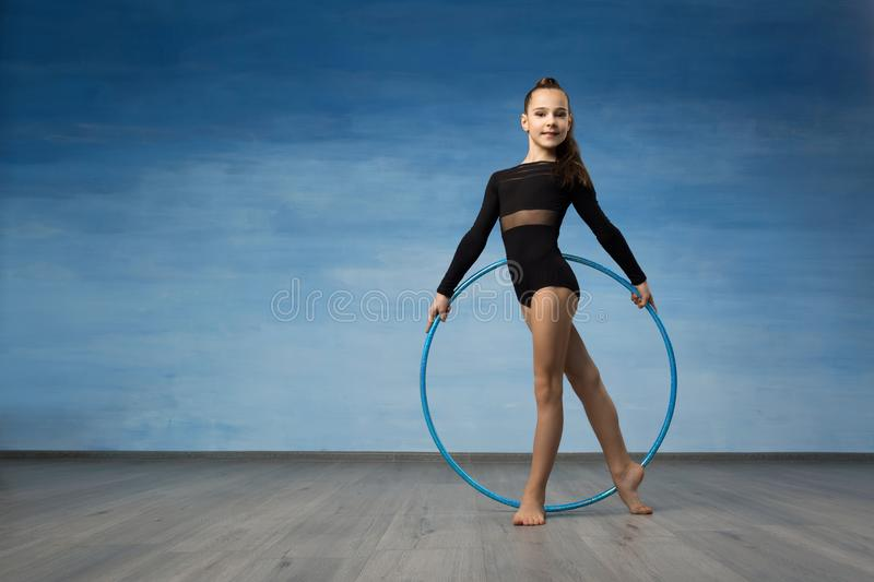 A girl gymnast in a black bathing suit looks in profile in the hands of a gymnastic hoop. stock images