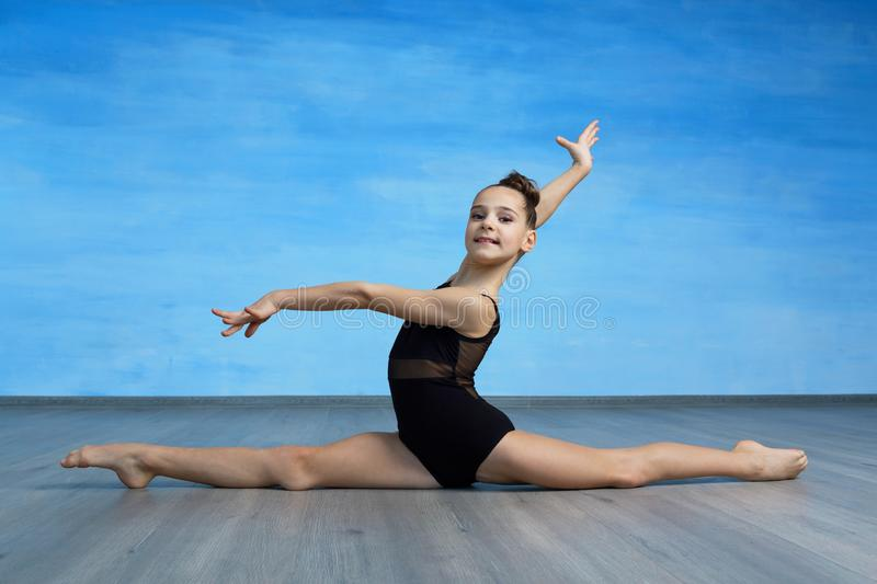 A girl gymnast in a black gymnastic swimsuit is sitting on a cross splits on the blue  background. stock images