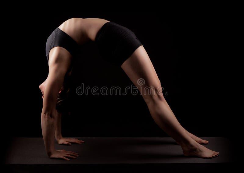 Gymnast yoga Chakrasana wheel pose. Girl in gymnast outfit doing the yoga Chakrasana or Urdhva Dhanurasana or also called Upward-Facing Bow Pose, wheel pose or royalty free stock photography
