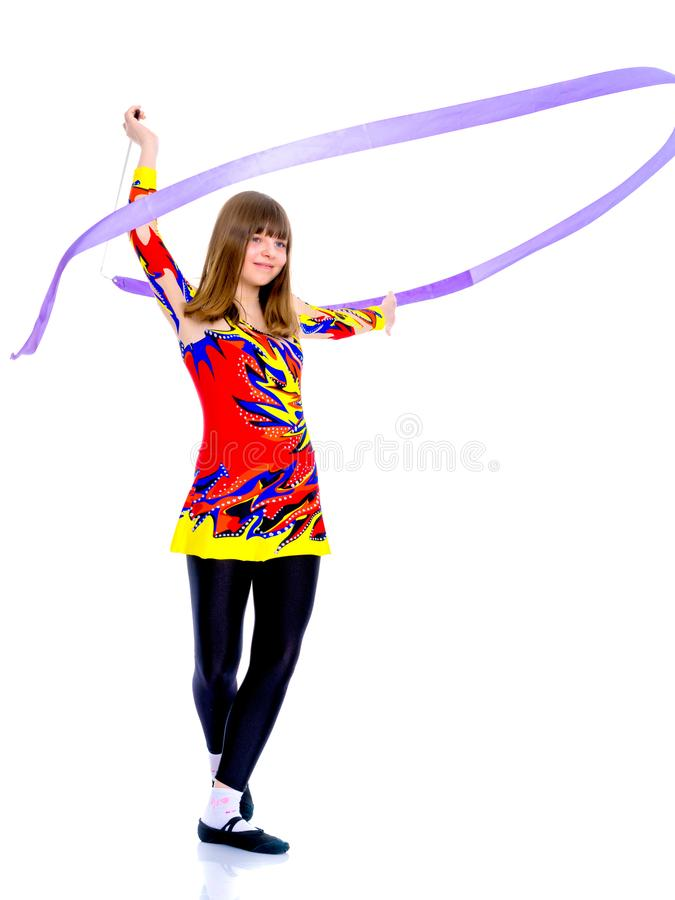 Girl gymnast performs exercises with tape. royalty free stock photos