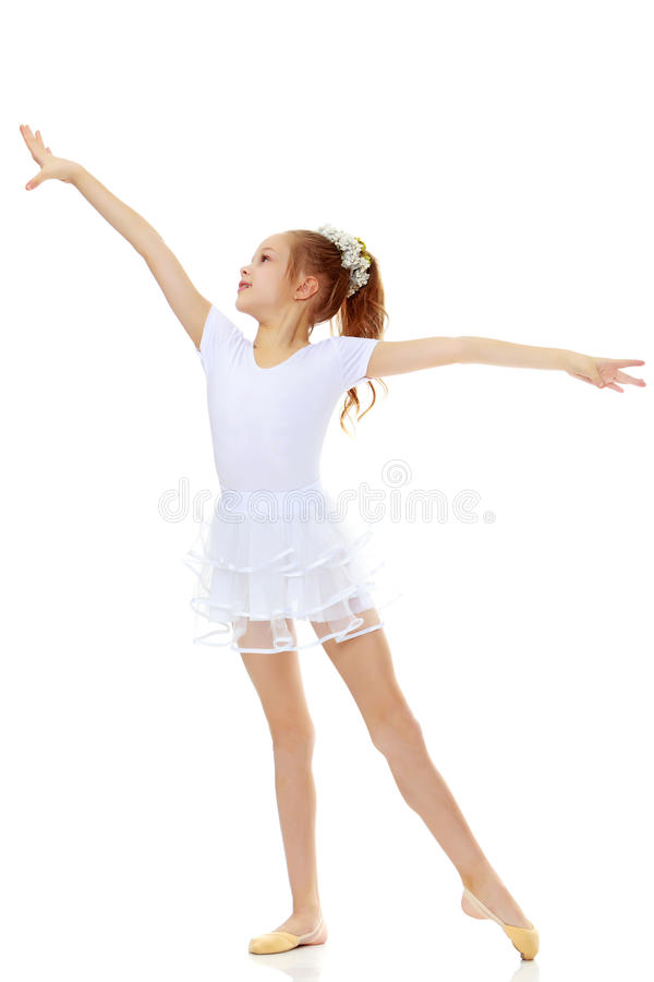 Girl gymnast waving his hands. Cheerful little girl gymnast in a white sports dress, posing in front of the camera.Isolated on white background royalty free stock photography