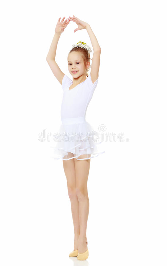 Girl gymnast waving his hands. Cheerful little girl gymnast in a white sports dress, posing in front of the camera.Isolated on white background royalty free stock photo