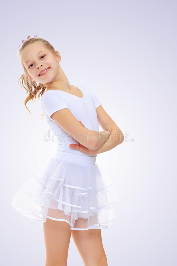 Girl gymnast in a white tracksuit. Beautiful little girl gymnast in a white sports suit poses for the camera stock photos