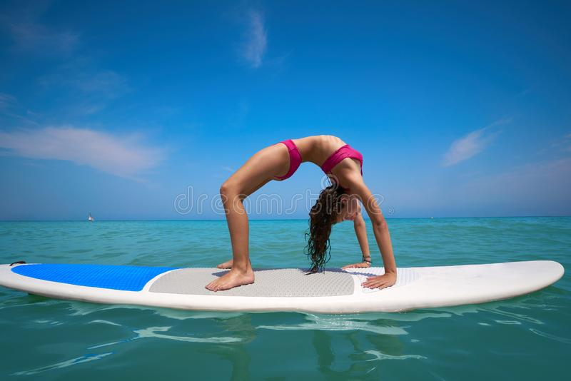 Girl gymnastics on paddle surf board SUP. In summer yoga stock photo