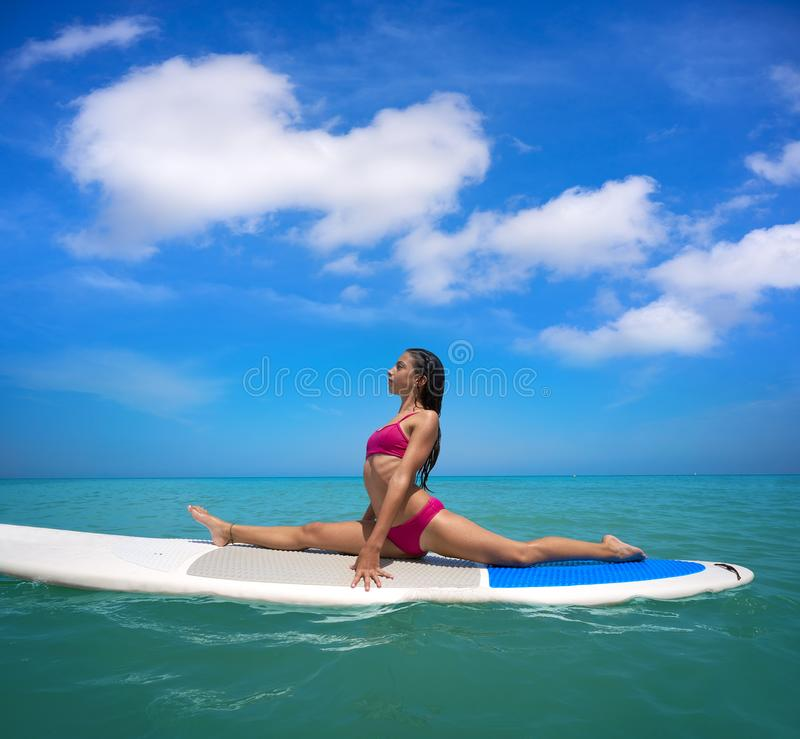 Girl gymnastics on paddle surf board SUP. In summer yoga royalty free stock photo