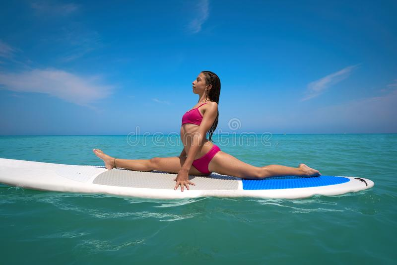 Girl gymnastics on paddle surf board SUP. In summer yoga royalty free stock photos