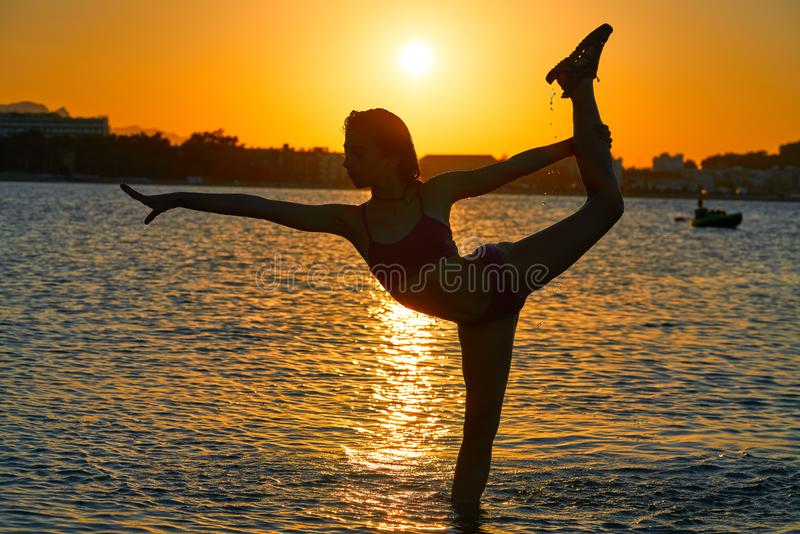 Girl gymnastics pose at sunset beach stock images