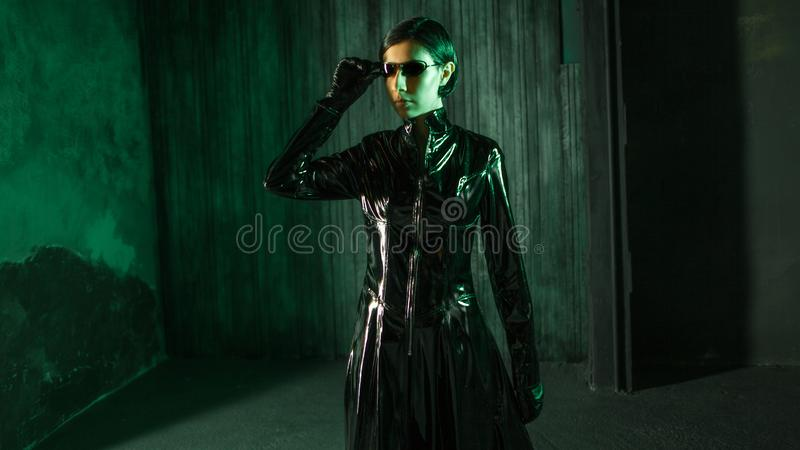 Girl hacker in the digital world. Young woman in matrix style suit. Black leather and sunglasses on black background royalty free stock photo