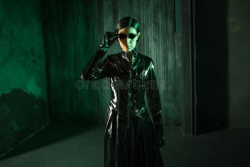 Girl hacker in the digital world. Young woman in matrix style suit. Black leather and sunglasses on black background stock image