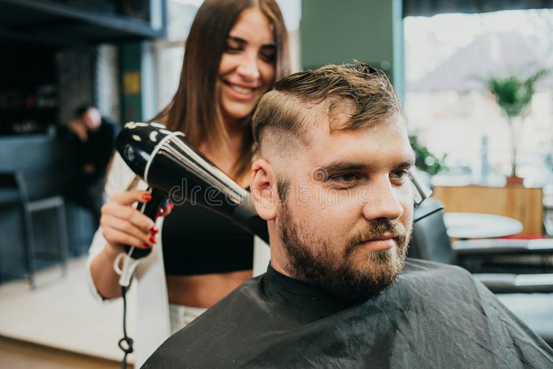 Girl hairdresser dries hair to a man in a salon royalty free stock photography