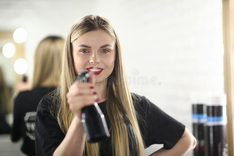 Girl Hairdresser Holding Water Sprayer Bottle. Woman Hairstylist with Spray in Beauty Salon. Beautician with Red Lips and Long Hair. Beauty Female with Fashion stock photo