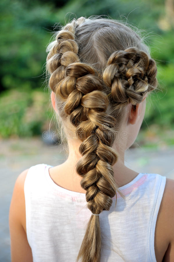 Girl hairstyle with French braid. Hairstyle with a French braid blonde girl hair royalty free stock photography
