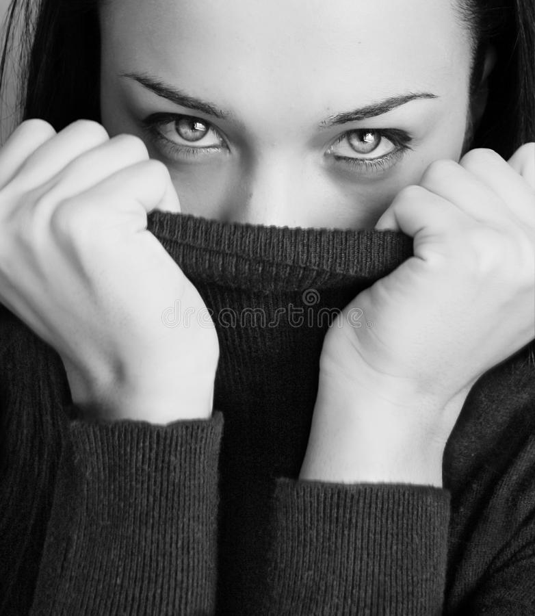 Girl with half face tighting pullover stock photography