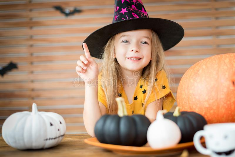 Girl in Halloween costume looking at camera, smiling and pointing up with her finger. Cute little girl wearing witch hat is sitting behind a table with royalty free stock images