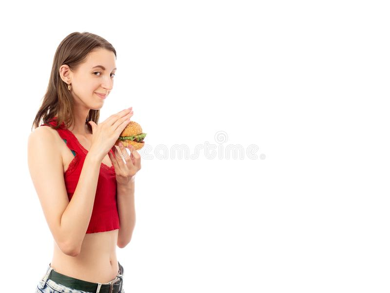Girl with hamburger. Happy shy young woman with hamburger on white background with copy space isolated looking at camera smiling royalty free stock photography