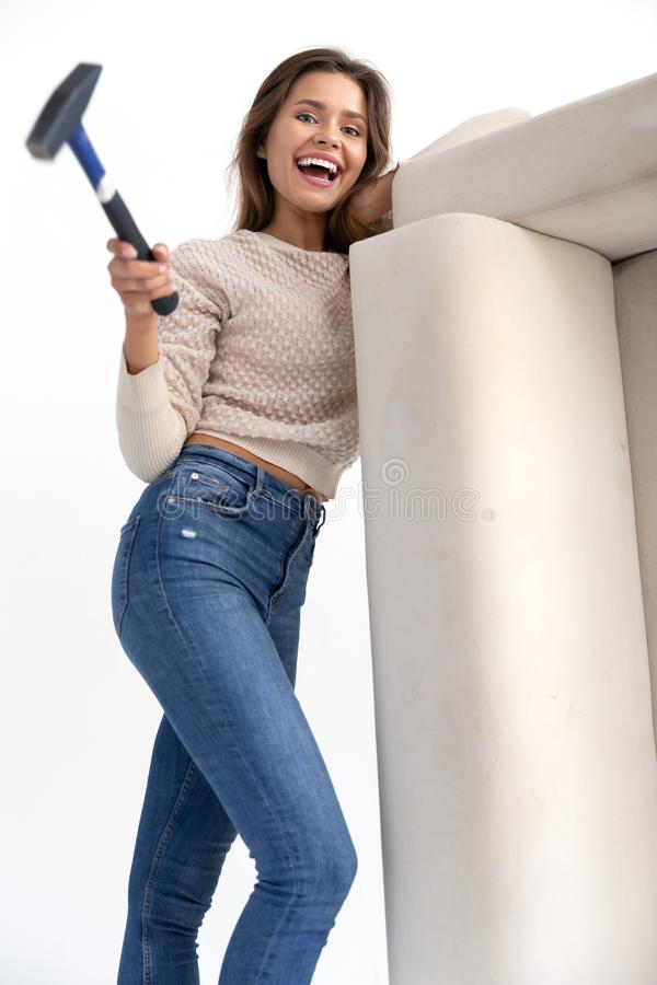 Girl with the hammer is fixing the sofa stock photo