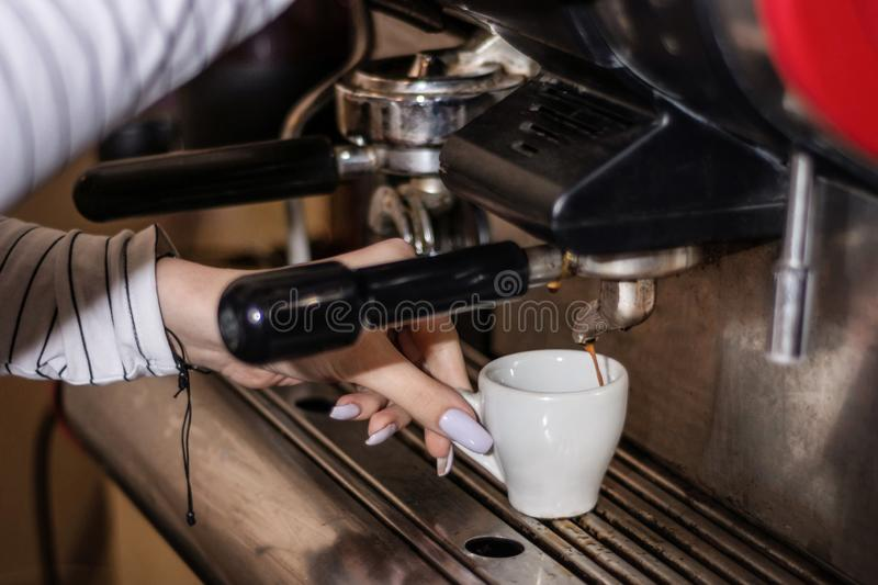 Girl hand with cup making espresso on the retro coffee machine in pub stock photography