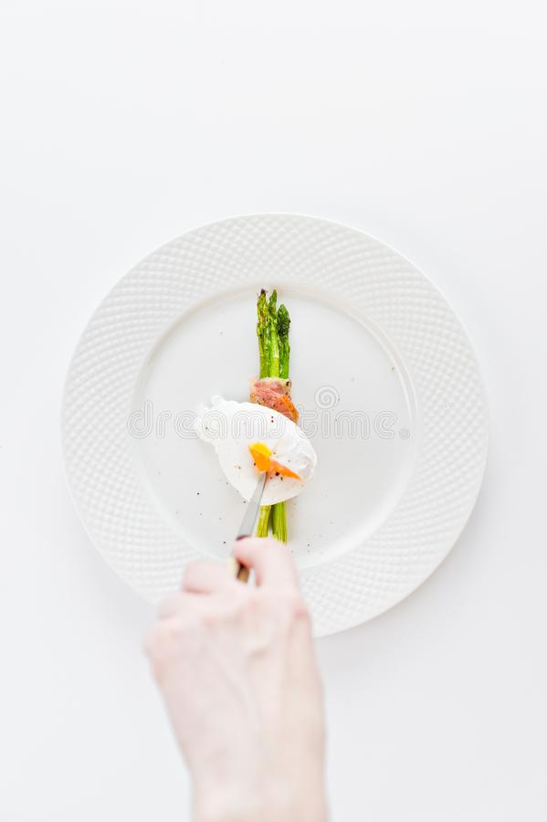 The girl hand cuts the poached egg on the grilled asparagus. stock photography