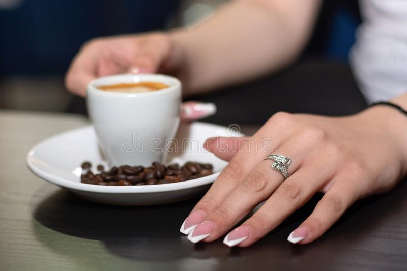 Girl hand with french nails polish manicure with espresso coffee cup on the desk in a bar on the saucer royalty free stock photos