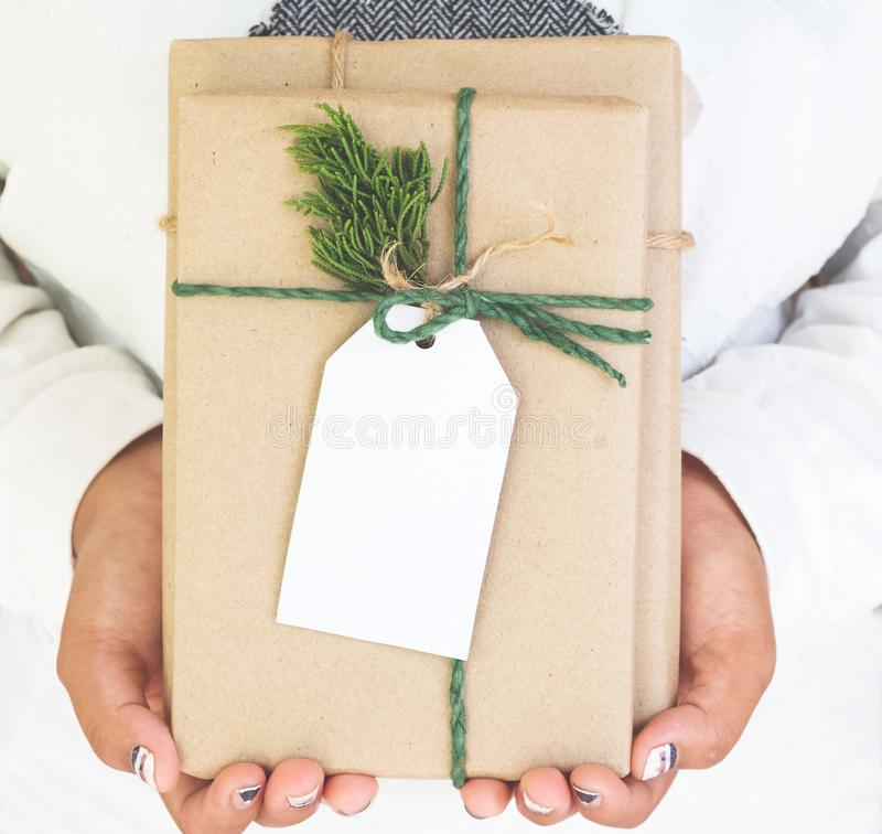 Girl hand holding craft and handmade christmas present gift boxes with tag. stock image