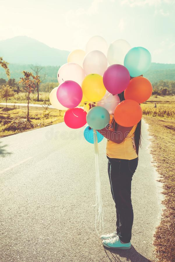 Girl hand holding multicolor balloons done with a retro instagram filter effect, royalty free stock photo
