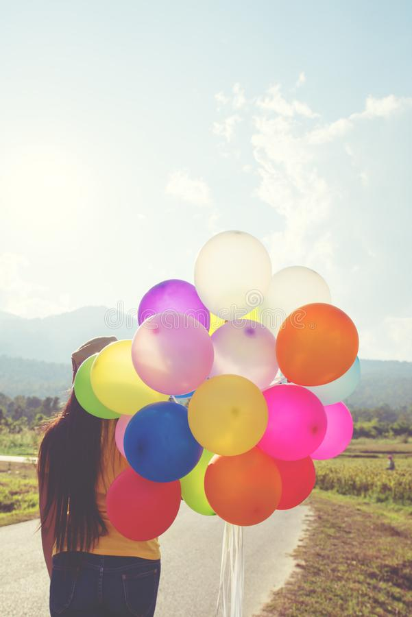 Girl hand holding multicolor balloons done with a retro instagram filter effect royalty free stock photos