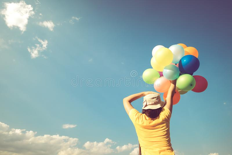 Girl hand holding multicolor balloons done with a retro instagram filter effect,. Concept of happy birth day in summer and wedding honeymoon party, Vintage stock images