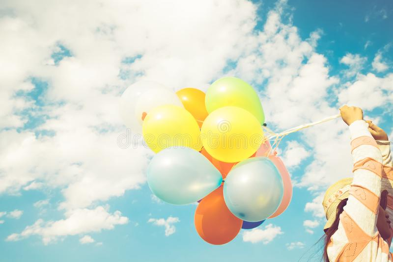 Girl hand holding multicolor balloons done with a retro instagram filter effect. Concept of happy birth day in summer and wedding honeymoon party, Vintage stock images