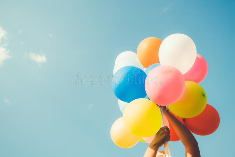 Girl hand holding multicolor balloons stock photography