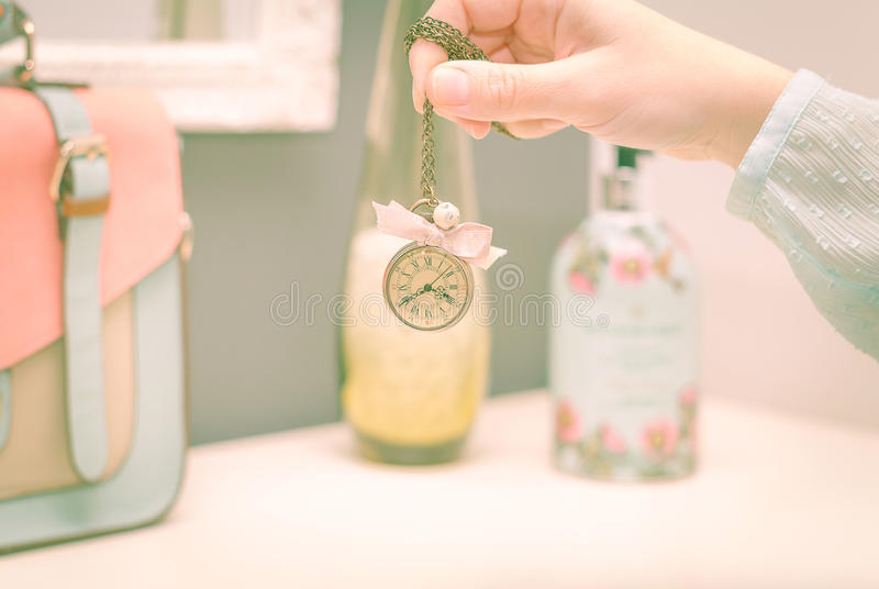 Girl hand holding a vintage clock necklace in front of female co royalty free stock photography