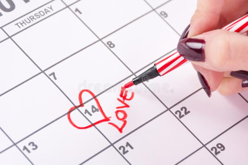 Girl hand with red felt pen drawing heart shape and writing word Love in calendar stock photo