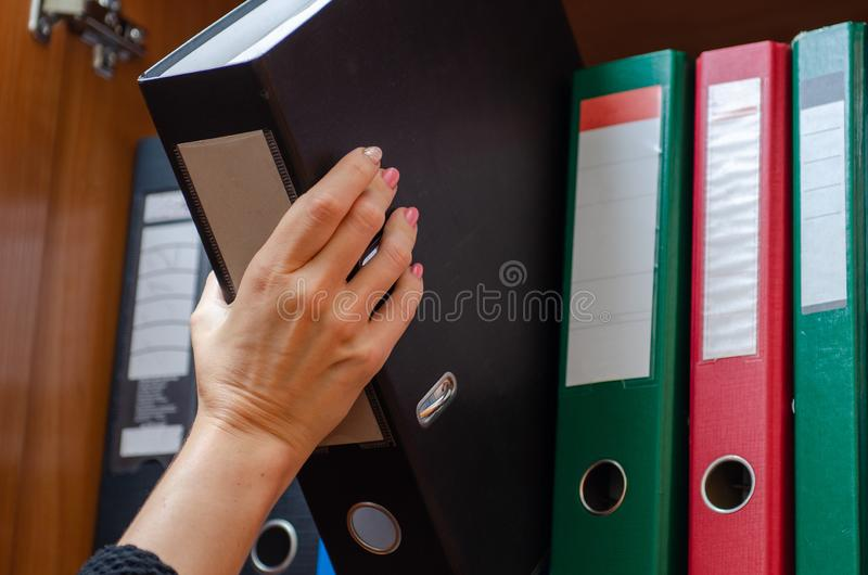 Girl hand takes folder from the shelf. Girl hand takes a folder from the shelf royalty free stock photos