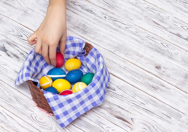 Girl hand takes multicolored Easter eggs from a basket on a white wooden background, Easter traditions and customs, spring. Copy space royalty free stock photo