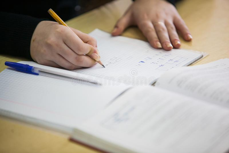 Girl hand writing down new information in exercise book stock photography