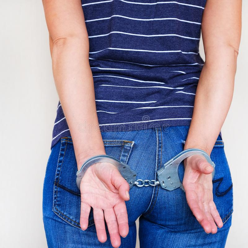 The girl in handcuffs at the police station. Arrested for misdemeanors stock images