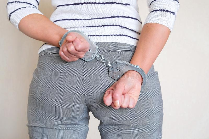 The girl in handcuffs at the police station. Arrested for misdemeanors stock photo
