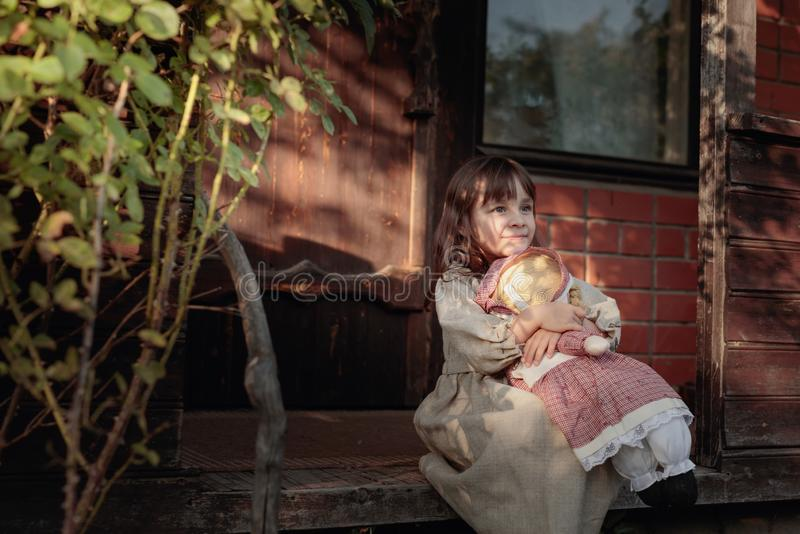 Girl with handmade doll on a summer evening near the old house royalty free stock photography