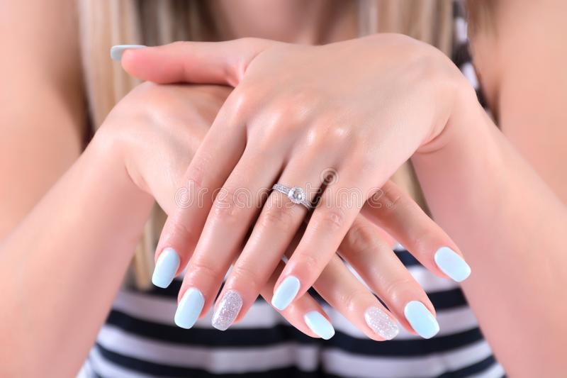 Girl hands with blue nails polish manicure and diamond engagement wedding rings. Beautiful young female hands and arms with blue nails polish manicure and royalty free stock images