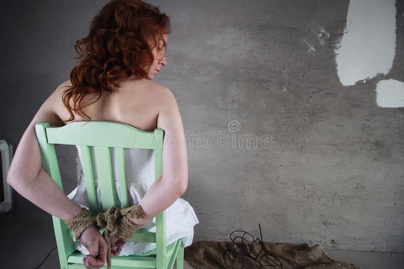 Girl hands bound prisoner. Portrait of a young red-haired girl on a background of gray plaster wall stock image