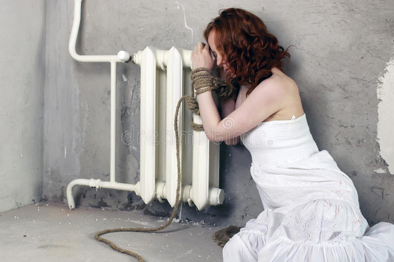 Girl hands bound prisoner. Portrait of a young red-haired girl on a background of gray plaster wall stock photography