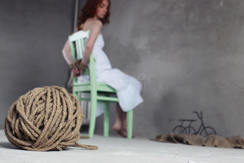 Girl hands bound prisoner. Portrait of a young red-haired girl on a background of gray plaster wall royalty free stock image