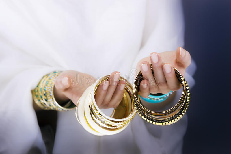 Girl hands with golden bracelets. On a white cloth stock image