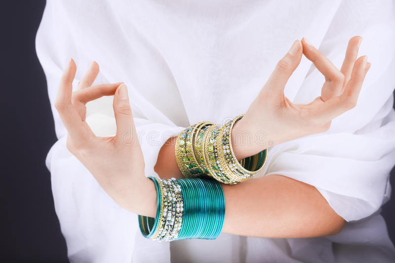 Girl hands with golden bracelets. On a white cloth royalty free stock image