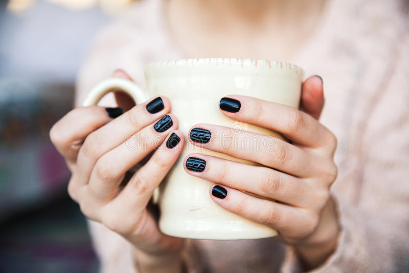 Girl hands holding a cup of coffee with beautiful black manicure. Christmas. And royalty free stock image