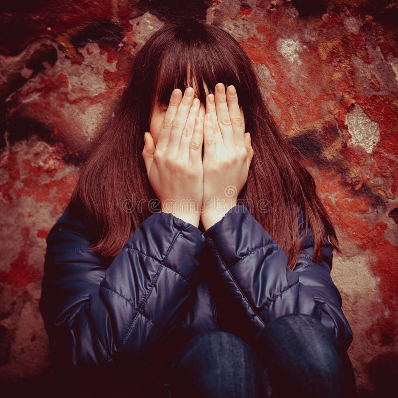 Girl with hands over eyes near wall outdoors stock images