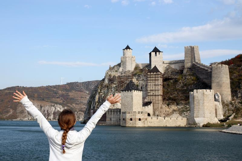 Girl with hands up looks at the Golubac fortress. Serbia royalty free stock images