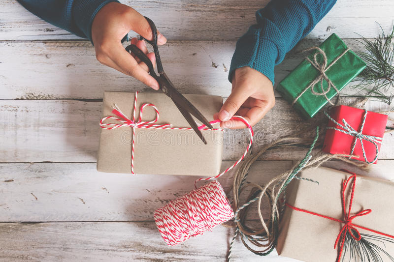 Girl hands wrapping gift for Christmas presents and New Year. stock photos