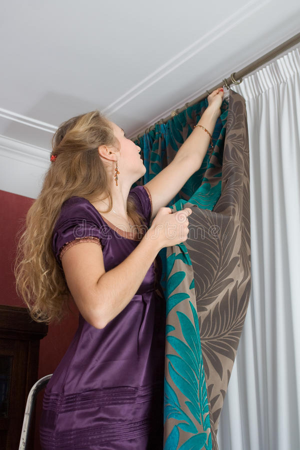 Girl hang up a curtain royalty free stock images
